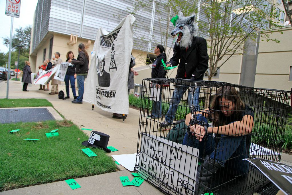 Lori Glover of Flint, Mich., sat in a cage at a protest outside an Energy Transfer Partners shareholders meeting at the Hilton Hotel in Dallas.