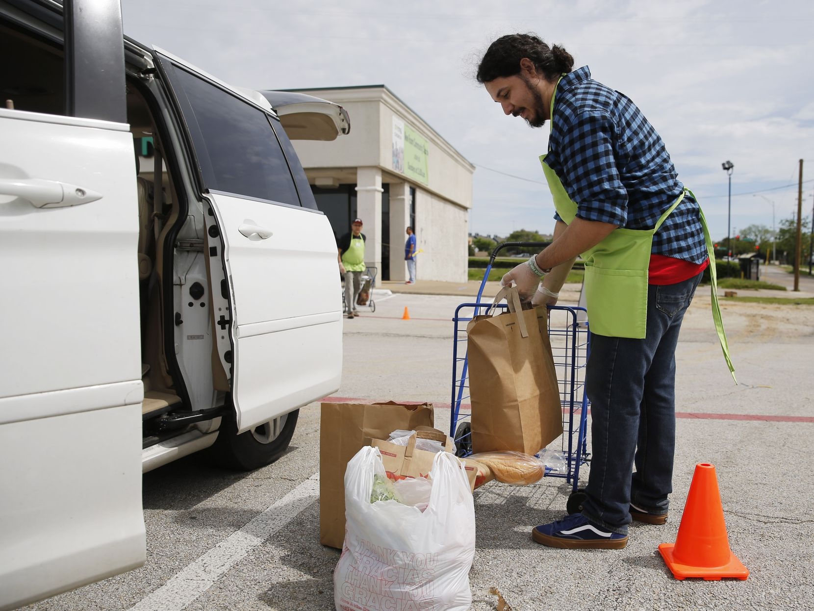 Rev. Juan Rios unloaded  groceries for people curbside outside of the New Room community church in Dallas on Wednesday, April 1, 2020. The New Room distributes food weekly to working-class families.