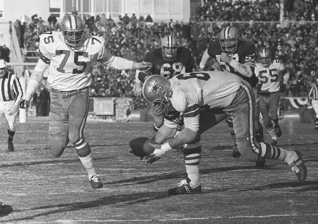 Dallas Cowboys defensive end George Andrie picks up a fumble and is about to follow teammate Jethro Pugh (75) into the end zone to score in the NFL Championship game against the Green Bay Packers on Dec. 31, 1967.  Played in sub-zero temperatures, the contest was later dubbed 'The Ice Bowl.'  (AP)