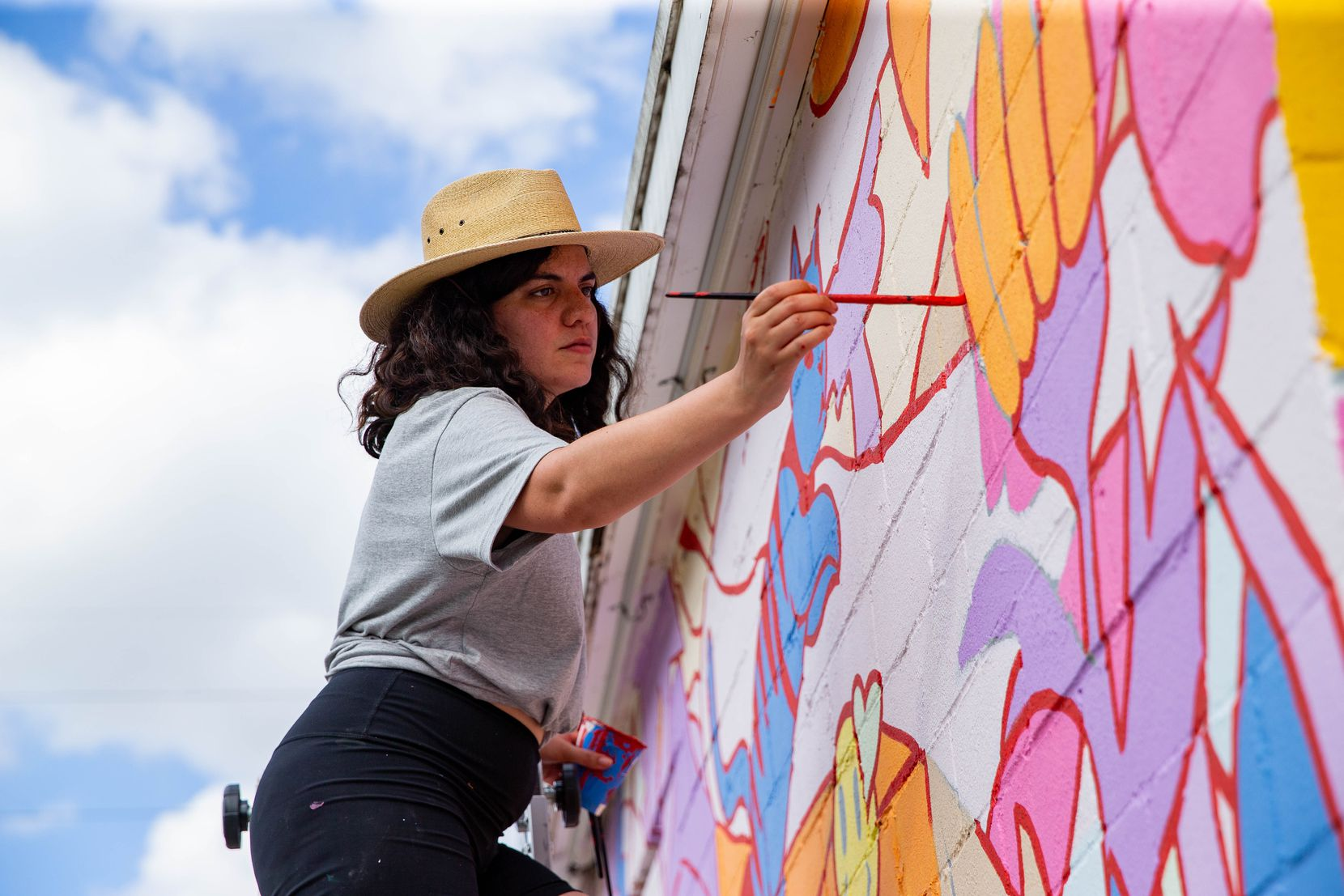 Artist Stephanie Sanz works on a mural with artist Brent Ozaeta (not pictured) as part of The Wild West Mural Fest in Dallas on Thursday, Oct. 22, 2020. The mural was inspired by a woman experiencing homelessness who walked by Sanz's apartment with a cat on a leash and plushies on her backpack.