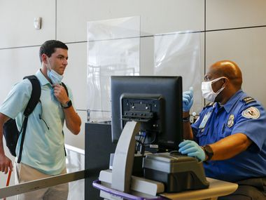 Transportation Security Officer Laymon Lightfoot (right) checks the travel documentation of Eric Hepler, 25, at DFW International Airport Terminal D on Friday, Sept. 3.