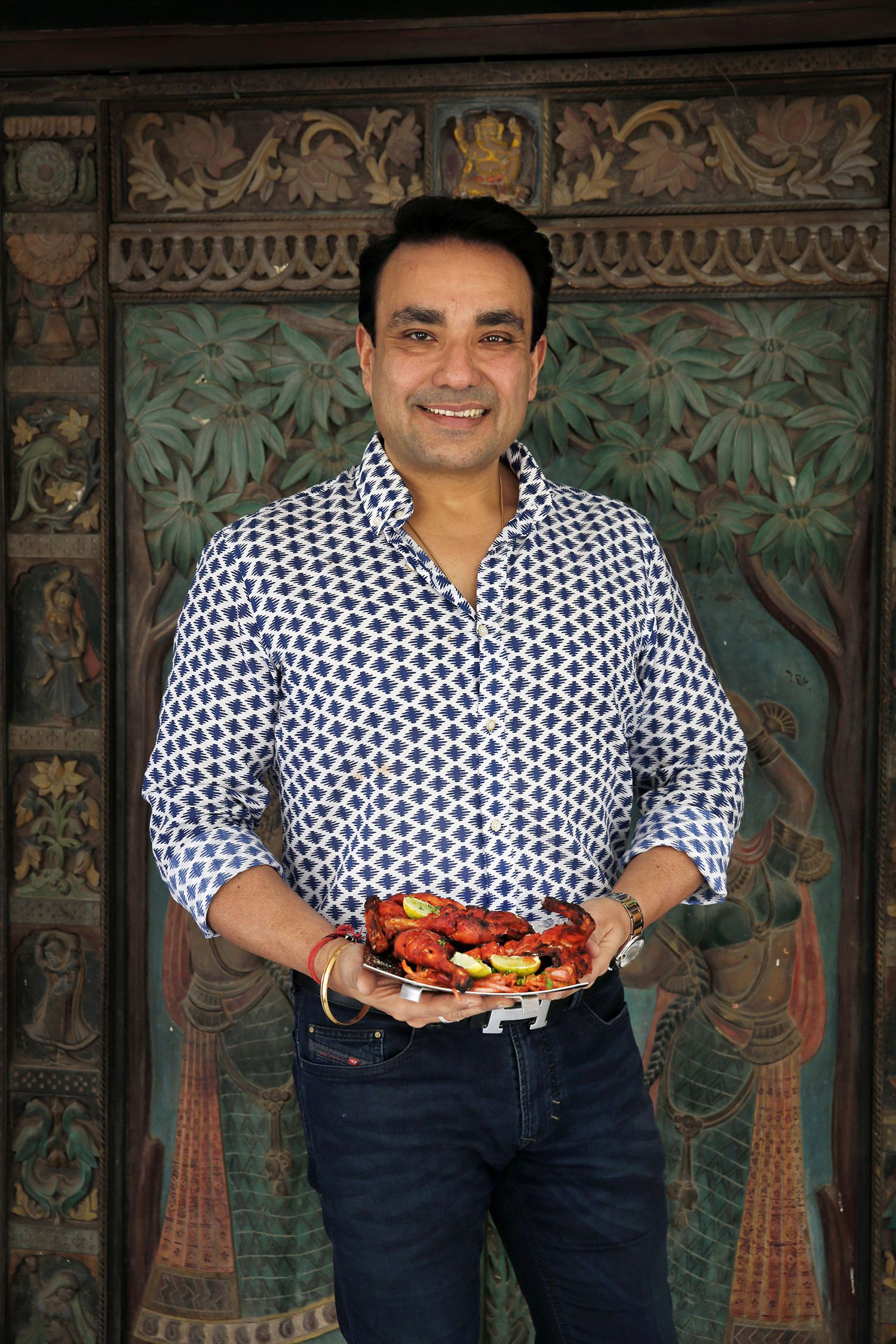 Monish Gujral of Moti Mahal restaurants holds a dish of butter chicken.