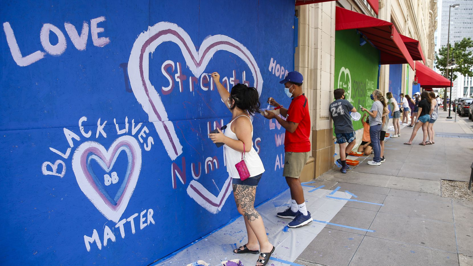 Bryana Otero, left, and Brannon Ridgley, both of Dallas, paint a mural on boarded-up windows at the Neiman Marcus on Saturday in downtown Dallas.