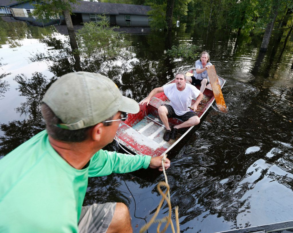 Brian Asbur (center) and Steve Casey (right) are towed in by Jody Anderson to speed up their trip back from checking on their mother's house after Hurricane Harvey near Vidor, Texas, on Sept. 3, 2017.