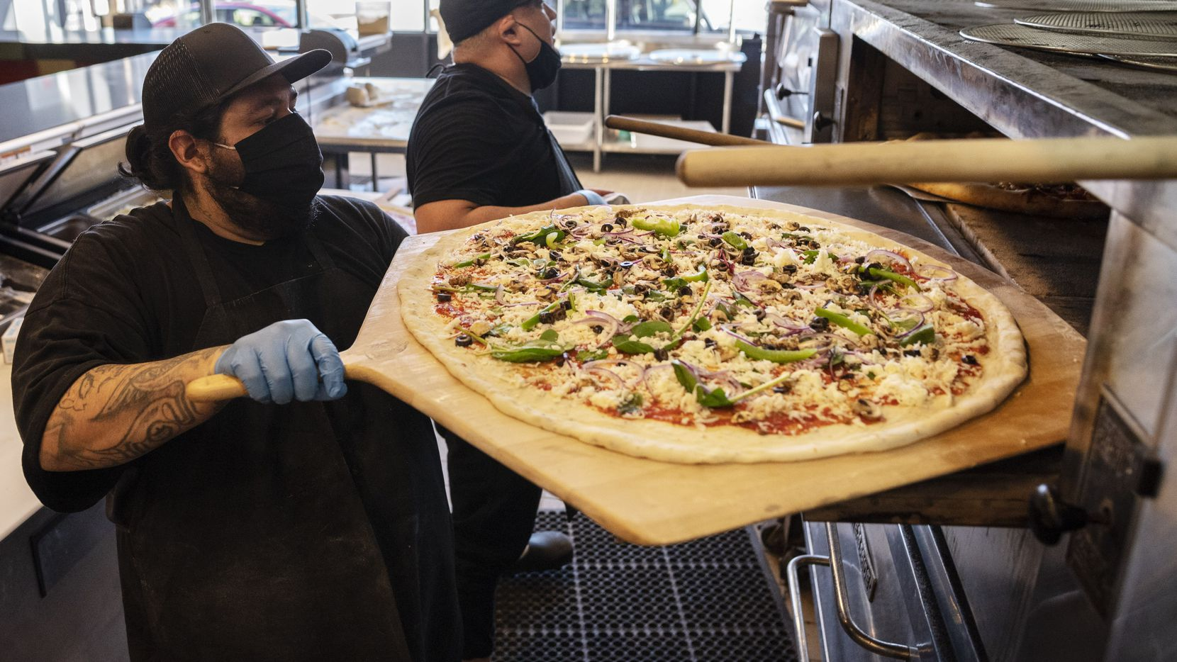 Juan Delgado, left, loads a veggie pizza into the oven while working alongside pizza maker Nick Flores, right, at the redesigned Serious Pizza in Deep Ellum. The Dallas restaurant reopened Feb. 26, 2021 under new ownership.
