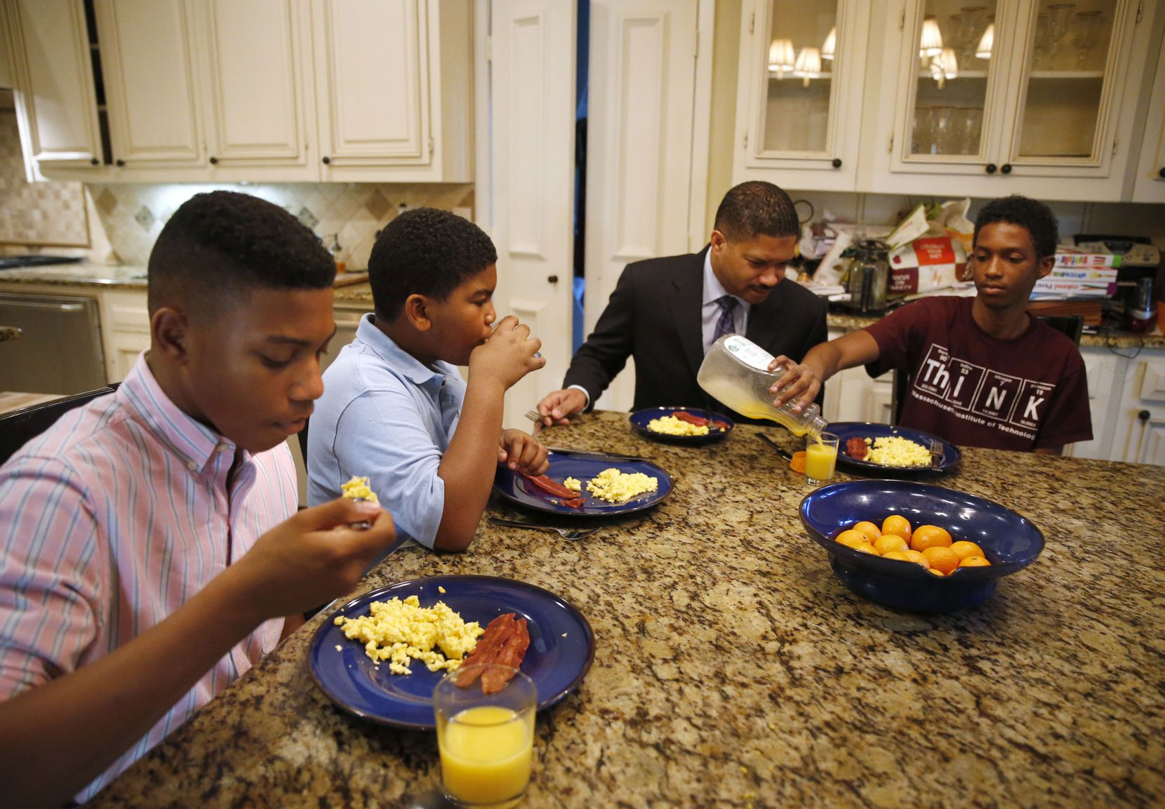 From left, William Waters, Christopher Waters and Joshua Waters eat breakfast with their father James, second from right, at their home in Dallas before heading off to school. (Vernon Bryant/Staff Photographer)