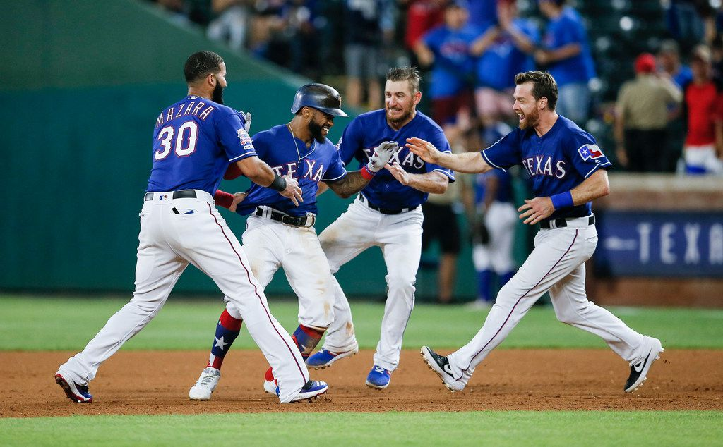 Texas Rangers' Delino DeShields, second from left, is congratulated by teammates after driving in the winning run with a single during the 12th inning of the team's baseball game against the Baltimore Orioles, Wednesday, June 5, 2019, in Arlington, Texas. Texas won 2-1. (AP Photo/Brandon Wade)