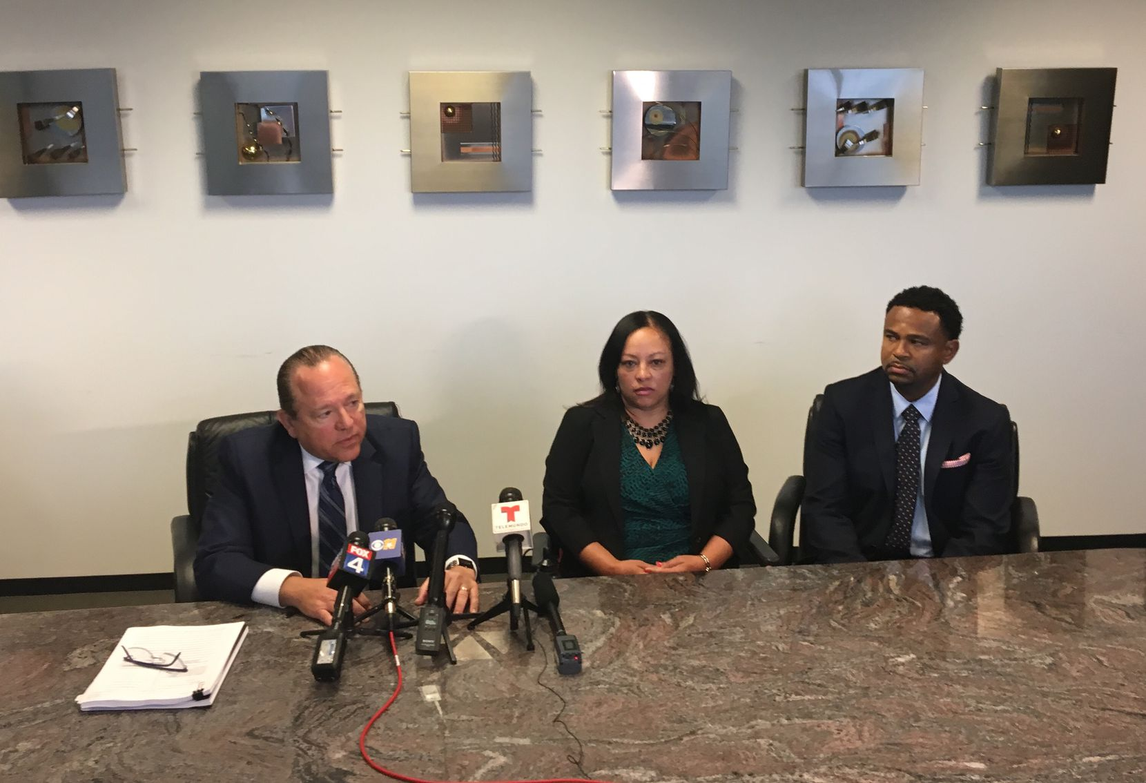 Hutton (center) at a news conference Friday.