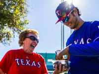 "Shirley Kost, also known as ""the cookie lady,"" gives a cookie to former Texas Rangers starting pitcher Yu Darvish (11)  during a spring training workout at the team's training facility on Thursday, February 16, 2017 in Surprise, Arizona."
