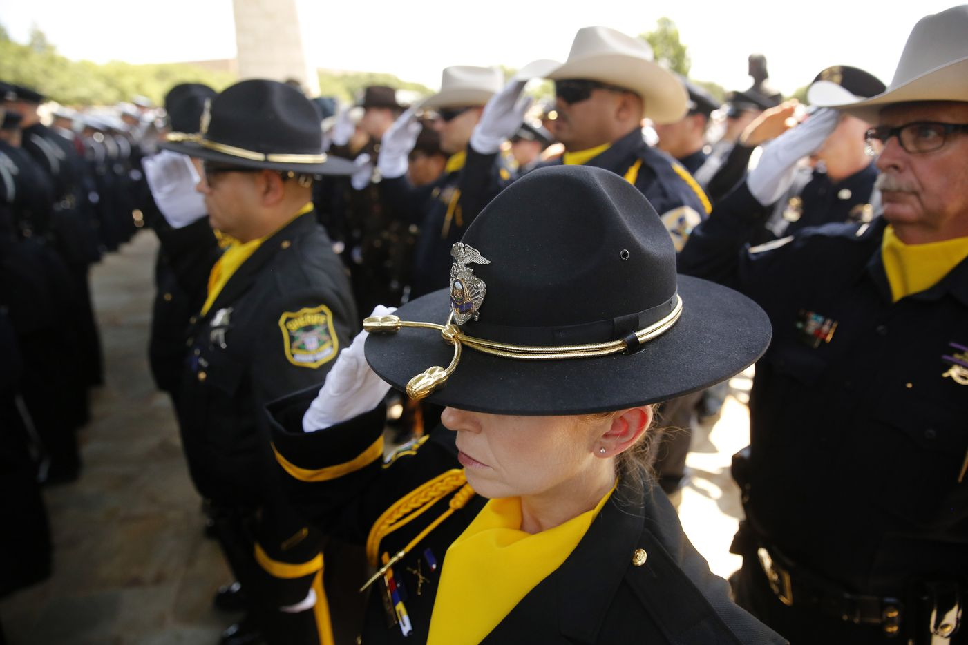 Sheriffs deputies salute as the casket of fallen Dallas police officer Lorne Ahrens is carried out of Prestonwood Baptist Church in Plano, Wednesday, July 12, 2016.