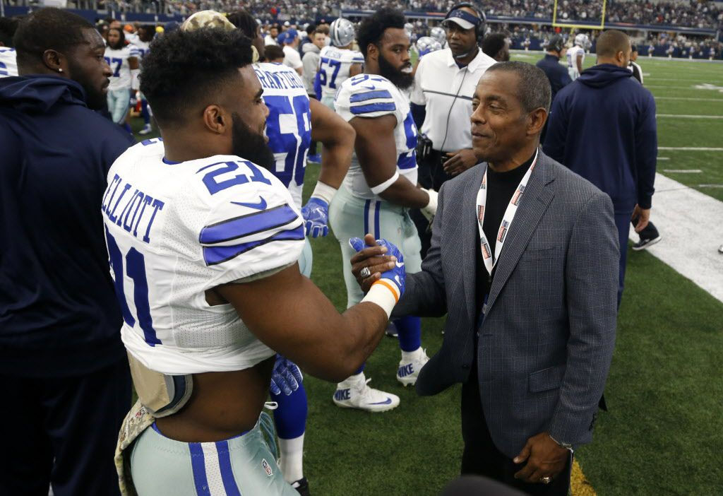 Dallas Cowboys running back Ezekiel Elliott shakes hands with Hall of Famer Tony Dorsett as the two chat on the sideline in the first half of an NFL football game against the Baltimore Ravens on Sunday, Nov. 20, 2016, in Arlington, Texas. (AP Photo/Michael Ainsworth)