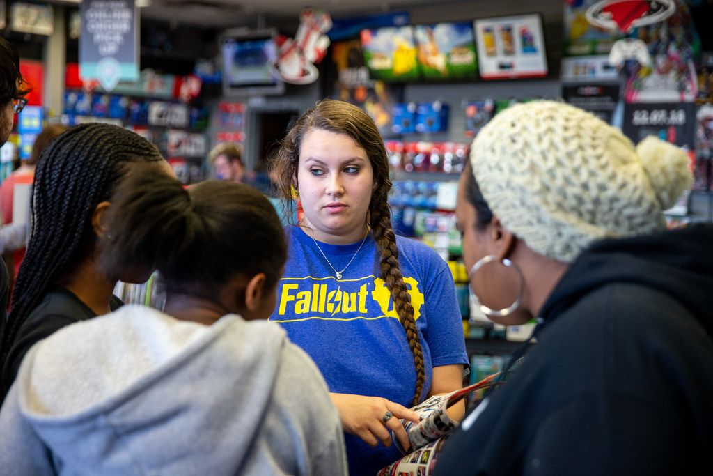 Bethany Edmondson helps customers find their games during Black Friday shopping at GameStop in Fairview on Thursday, November 22, 2018.