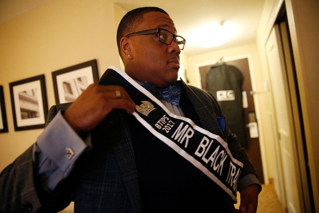 Trenton Johnson, a transgender man, puts on his Mr. Black Trans International sash before the Black Trans Advocacy Conference gala in his hotel room at the Dallas/Addison Marriott Quorum by the Galleria in Dallas on Friday.