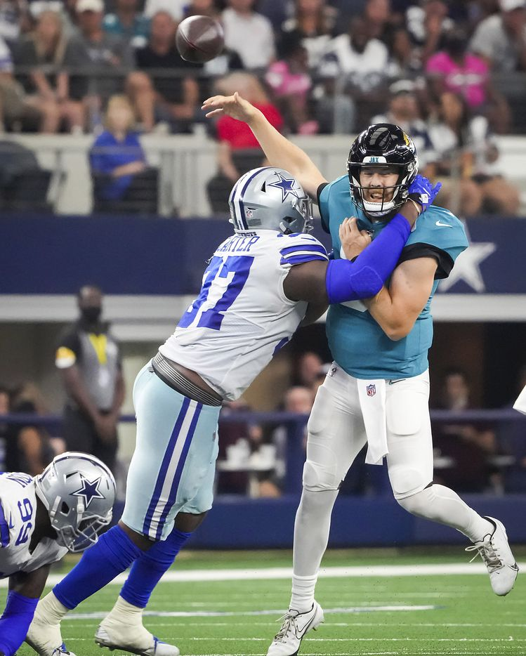 Jacksonville Jaguars quarterback C.J. Beathard (3) throws an interception as he is hit by Dallas Cowboys defensive end Ron'Dell Carter (97) during the first half of a preseason NFL football game at AT&T Stadium on Sunday, Aug. 29, 2021, in Arlington. (Smiley N. Pool/The Dallas Morning News)