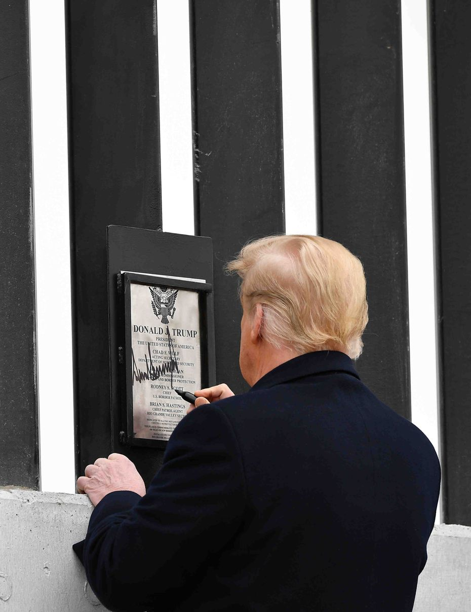 US President Donald Trump autographs a plaque on a section of the border wall in Alamo, Texas on January 12, 2021.