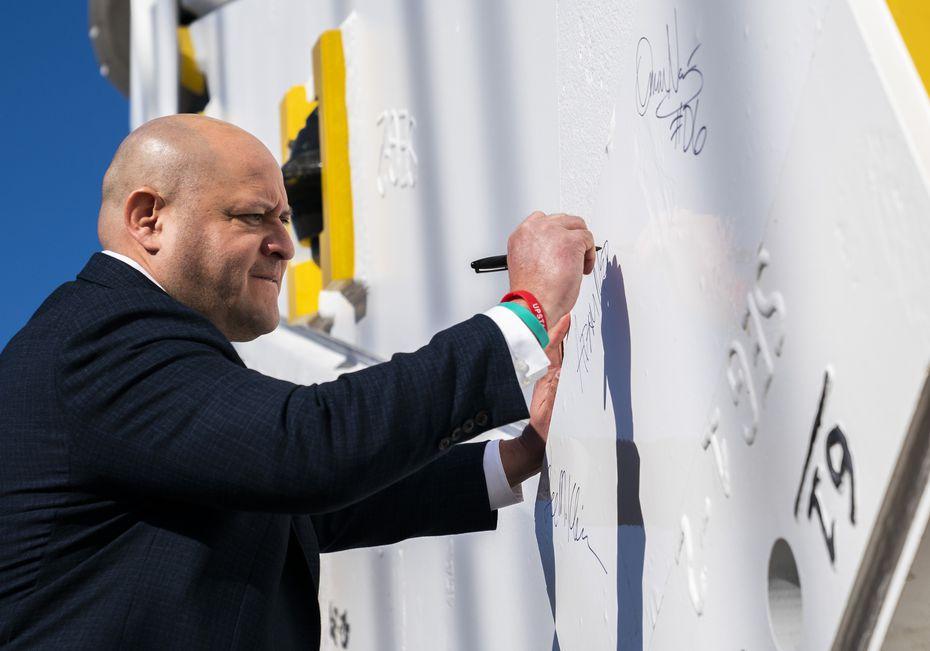 El concejal Adam Medrano firma su nombre en el taladro gigante que excavará cinco millas por debajo de la ciudad.