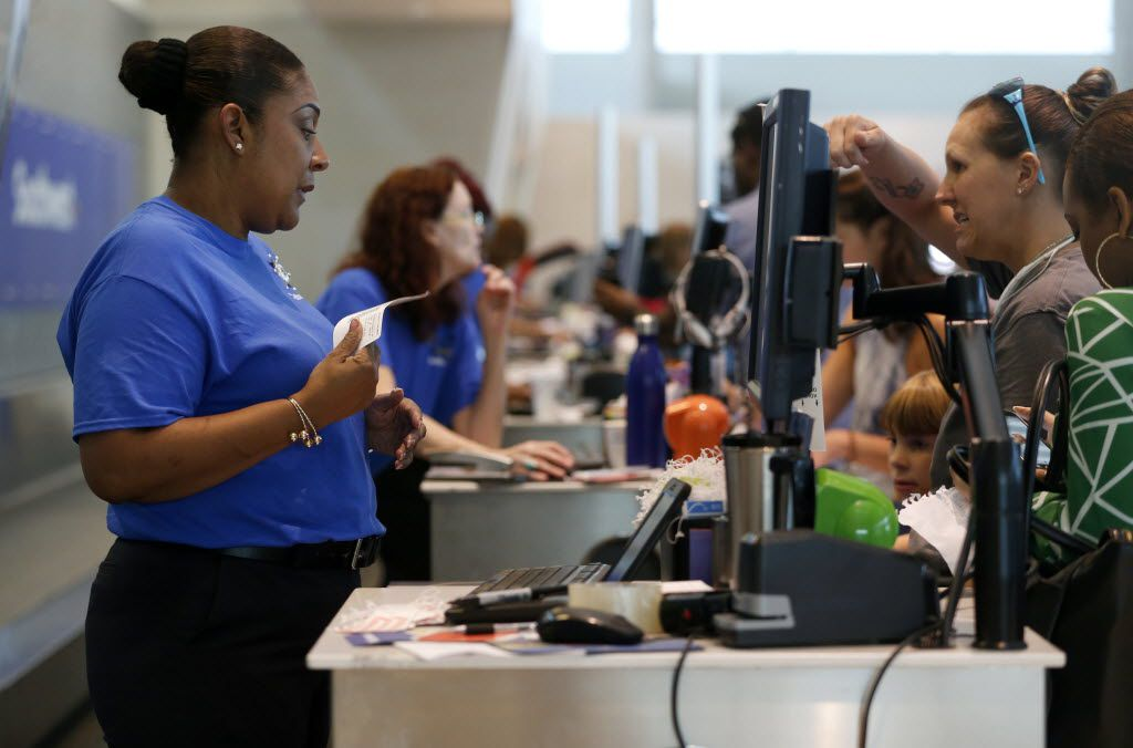 Sharlene, a customer service agent for Southwest Airlines, checked in a passenger at the Southwest Airlines terminal at Dallas Love Field Airport last week. Technical issues disrupted Southwest' operations, grounding flights and causing long lines at airports across the country. (Rose Baca/Staff Photographer)
