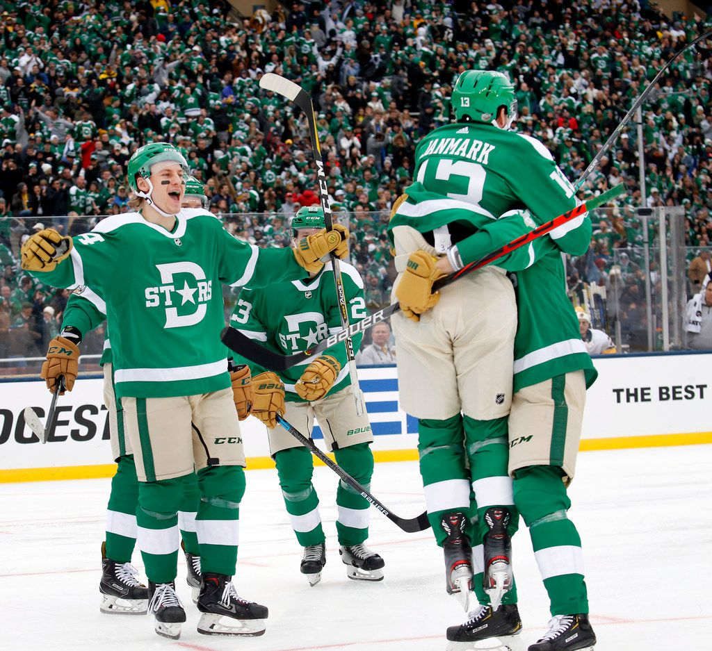 Dallas Stars center Mattias Janmark (13) jumps into the arms of defenseman John Klingberg (3)  after scoring during the third period of the NHL Winter Classic hockey game at the Cotton Bowl in Dallas, Wednesday, January 1, 2020. The Stars came back to win, 4-2. (Tom Fox/The Dallas Morning News)