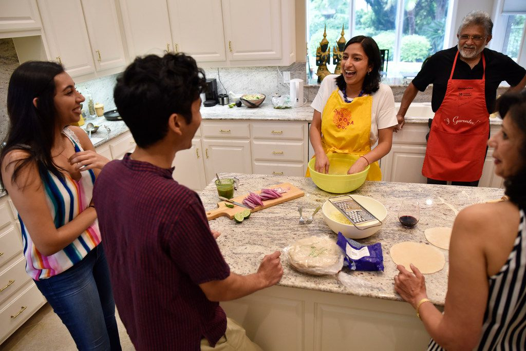 Priya Krishna, right, speaks to her cousins Meha Elhence, 21, Hirsh Elhence, 24, and her parents Ritu Krishna, bottom-far-right, and Shailendra Krishna, top-right, as they prepare dishes.