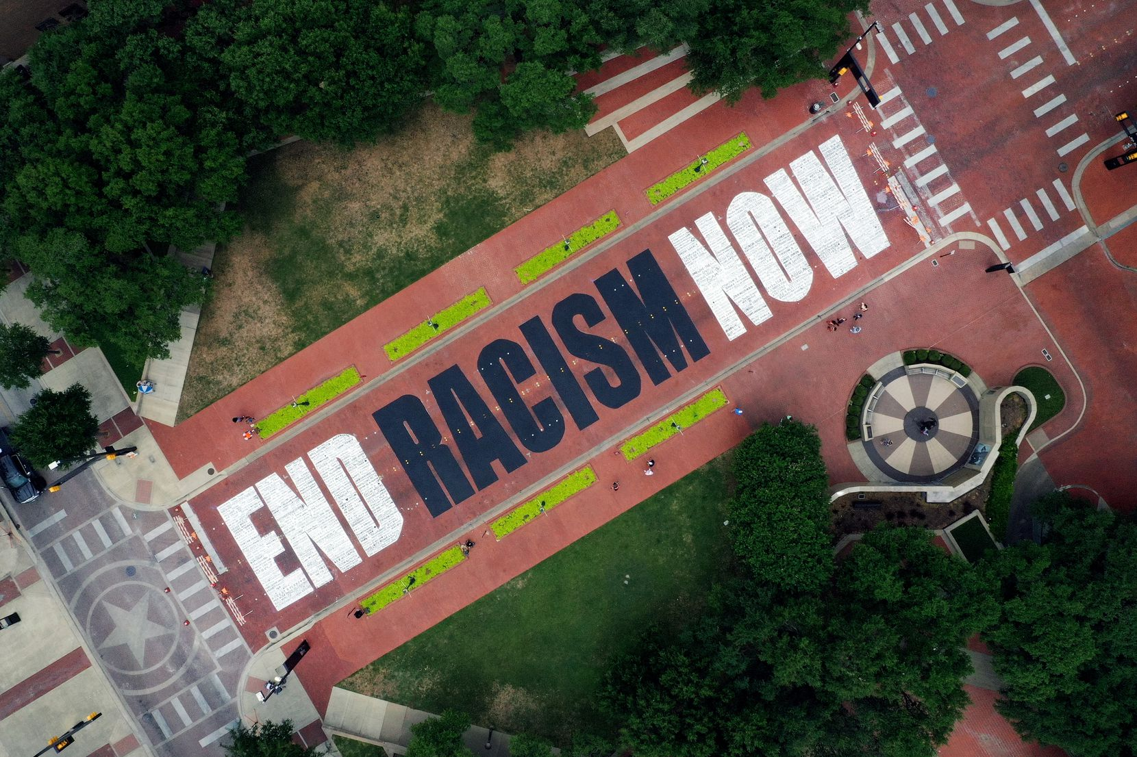 "FORT WORTH, TEXAS - JUNE 28: An aerial view from a drone as residents view the ""End Racism Now"" mural painted on Main Street in downtown on June 28, 2020 in Fort Worth, Texas. Local artists partnered with volunteers to paint the message after being inspired by the Black Lives Matter movement and recent protest following the death of George Floyd. (Photo by Tom Pennington/Getty Images)"