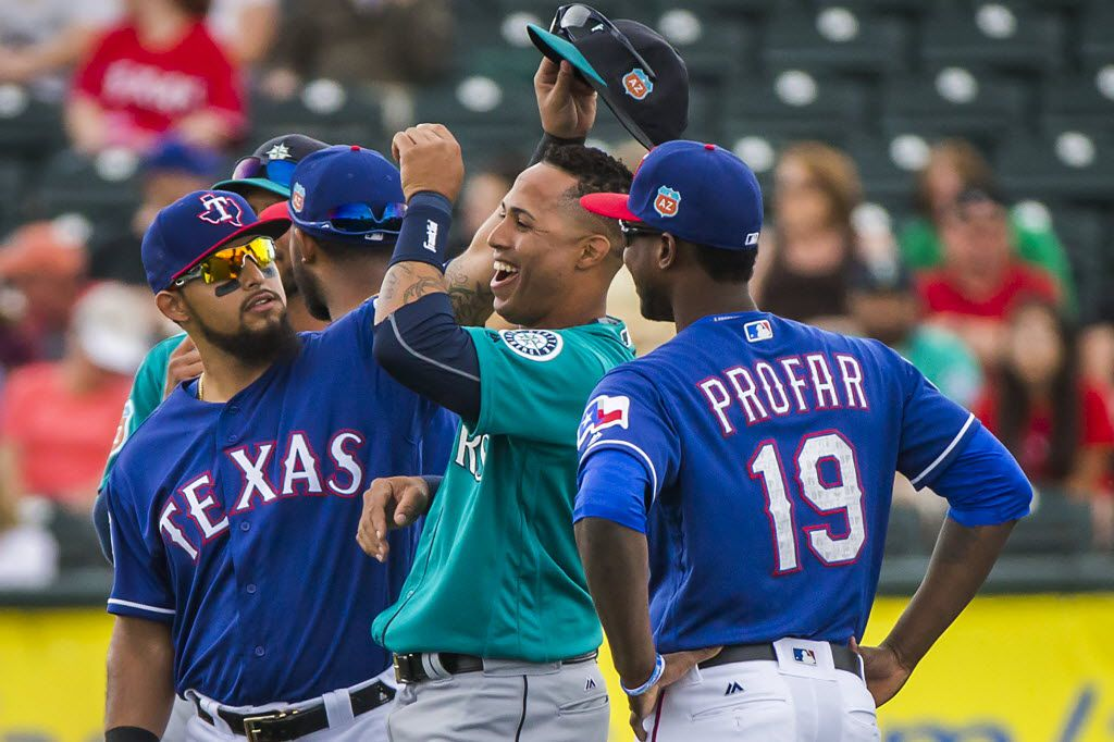 Texas Rangers second baseman Rougned Odor lifts the cap of Seattle Mariners center fielder Leonys Martin to check out his hairdo as the teams warm up before a spring training game at Surprise Stadium on Sunday, March 6, 2016, in Surprise, Ariz. (Smiley N. Pool/The Dallas Morning News)