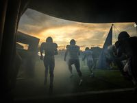 Frisco Lone Star players take the field to face Highland Park in a high school football game as the sun sets on Highlander Stadium in University Park.