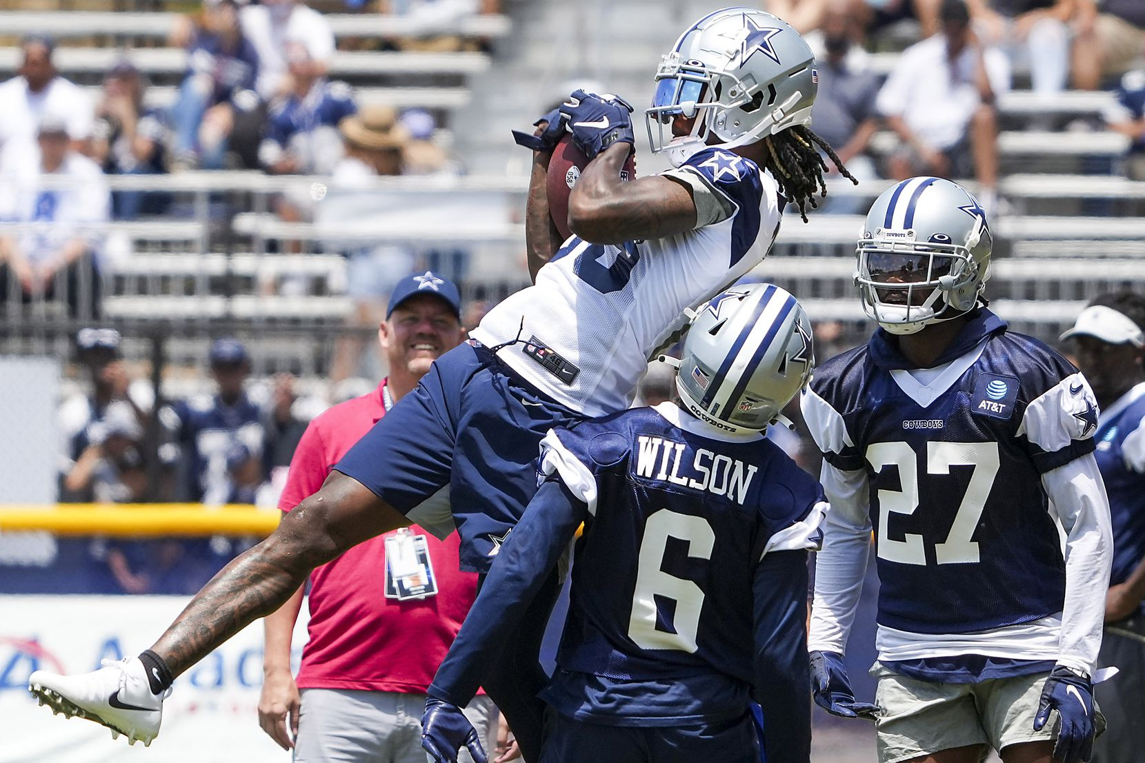 Dallas Cowboys wide receiver CeeDee Lamb (88) makes a catch over safety Donovan Wilson (6) and cornerback Trevon Diggs (27) during a practice at training camp on Tuesday, July 27, 2021, in Oxnard, Calif.