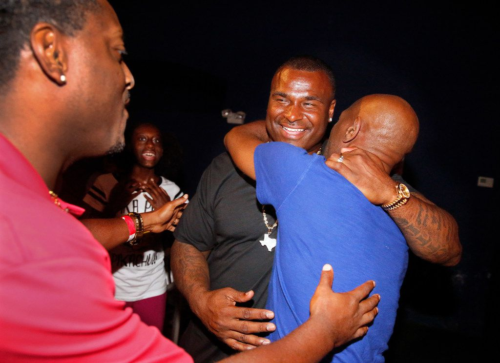 Former Carter and NFL football player Jessie Armstead (center) is greeted by old friends Terrence Williams (left) and Clifton Abraham following the premiere of What Carter Lost, an ESPN documentary about the 1988 Carter football team, at the Texas Theatre in Dallas.