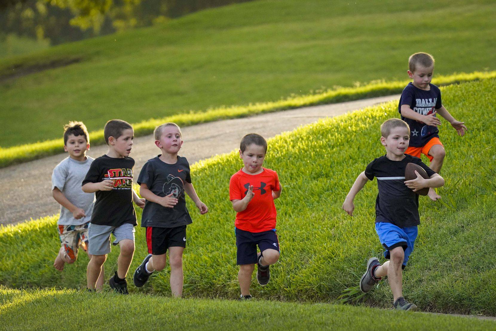 Grant Bass, 6, races down the sidewalk with a football while chased by other neighborhood children in Canyon Creek subdivision on Thursday, July 2, 2020, in Richardson.