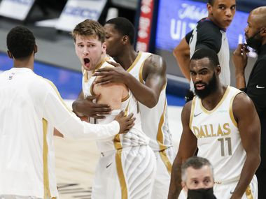 Dallas Mavericks guard Luka Doncic (77) is held back by teammates while arguing a call at the end of the first half of an NBA basketball game against the Utah Jazz in Dallas, Monday, April 5, 2021.
