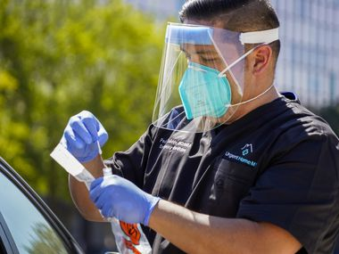 Dr. Pedro Salcido, of Urgent Home MD, conducts a COVID-19 drive-thru test in a downtown parking lot on Tuesday, Aug. 18, 2020, in Dallas. (Smiley N. Pool/The Dallas Morning News)