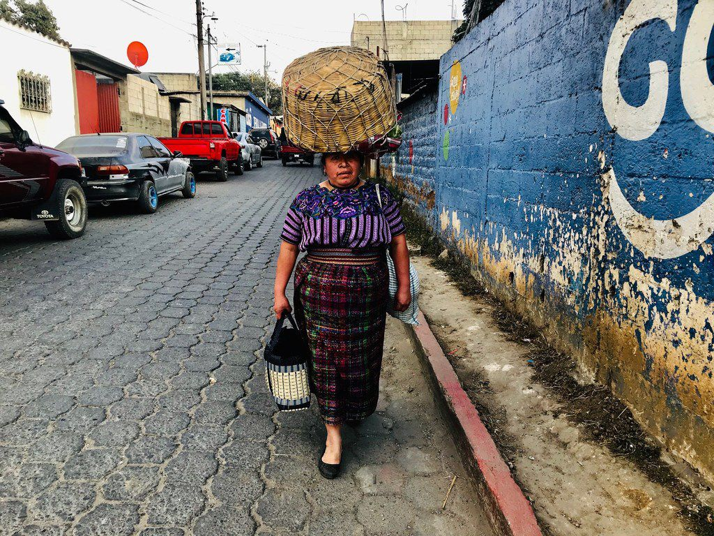 A woman in traditional indigenous dress walks the streets of San Martin Jilotepeque, Guatemala. She confuses a visitor for a smuggler and asks him to leave her alone.