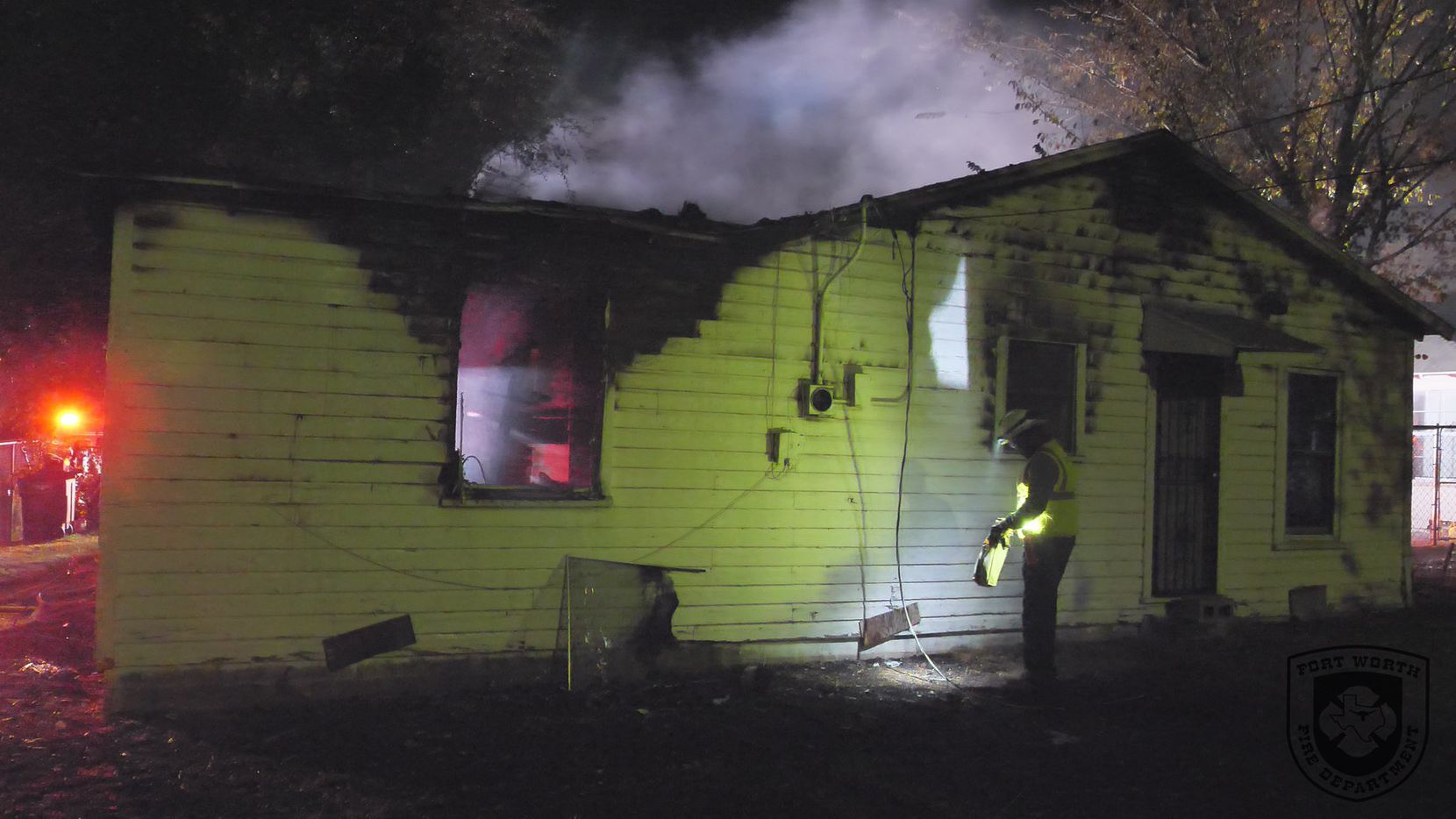 A firefighter examines a home damaged by fire Wednesday morning in Fort Worth. One woman inside was rescued and was hospitalized in serious condition.