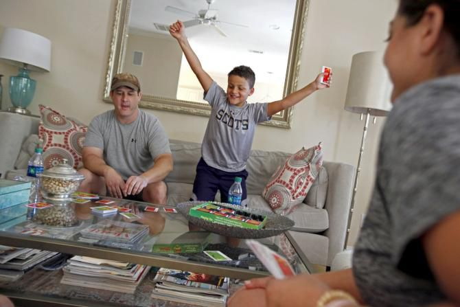Maryam Morse (right) worried that being glued to a computer or TV screen wasn't healthy for her sons. Jack recently played a card game with his dad, Mike.