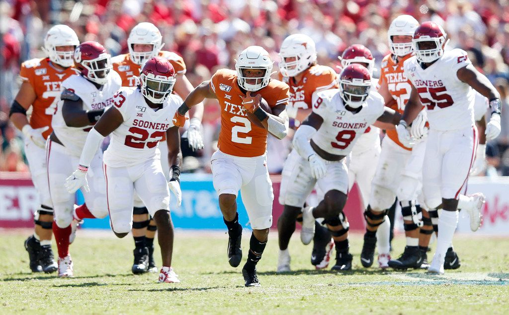 Texas Longhorns quarterback Roschon Johnson (2) runs up the field for a big play as Oklahoma Sooners defense chases after him during the second half of play in the Red River Showdown at the Cotton Bowl in Dallas on Saturday, October 12, 2019. Oklahoma Sooners defeated Texas Longhorns 34-27.
