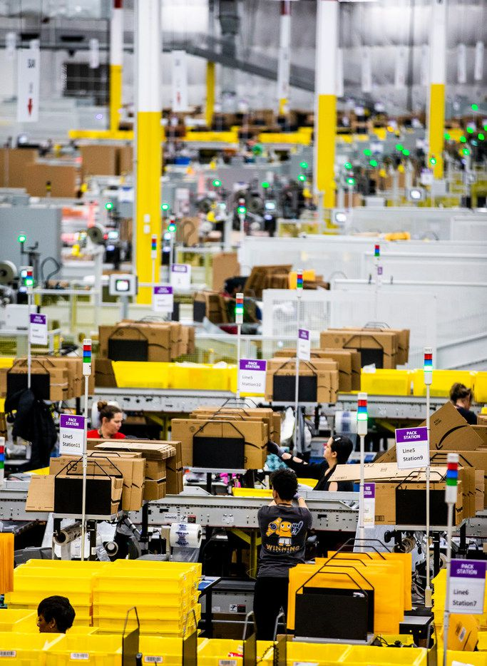 Employees sort and move packages at an Amazon fulfillment center in Grapevine.
