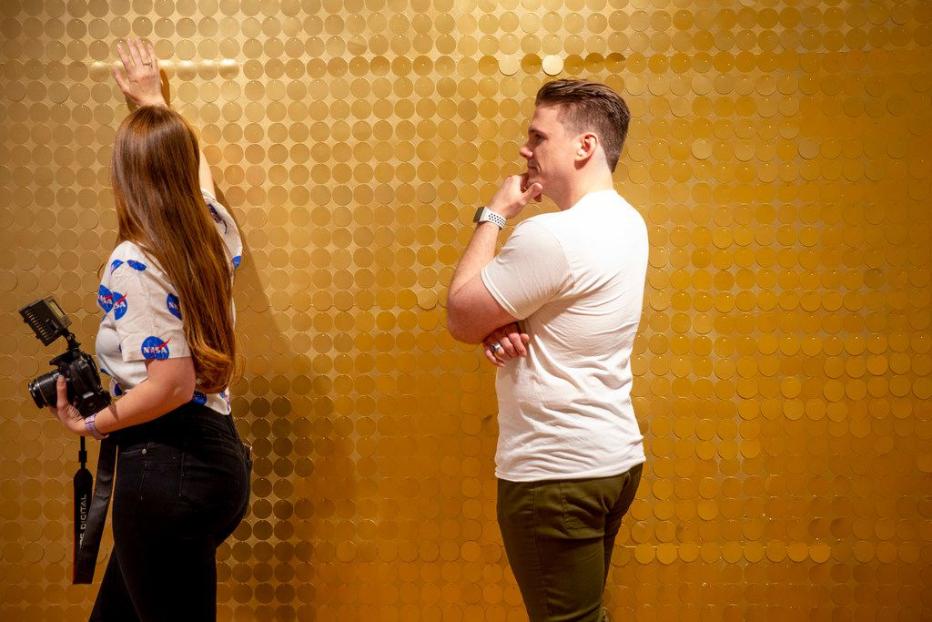 Joshlyn Davis, left, shows Alex Russian how to pose as she gets ready to take his picture at the Snap151 in Dallas on Friday, April 5, 2019. Snap151 is an interactive photo studio. (Shaban Athuman/Staff Photographer)