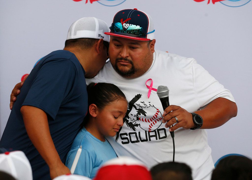 Ray Garcia (left) of El Paso hugged Danny Latin) and his daughter at the end of the candlelight vigil at The Sportspark in El Paso on Sunday, Aug. 4, 2019.