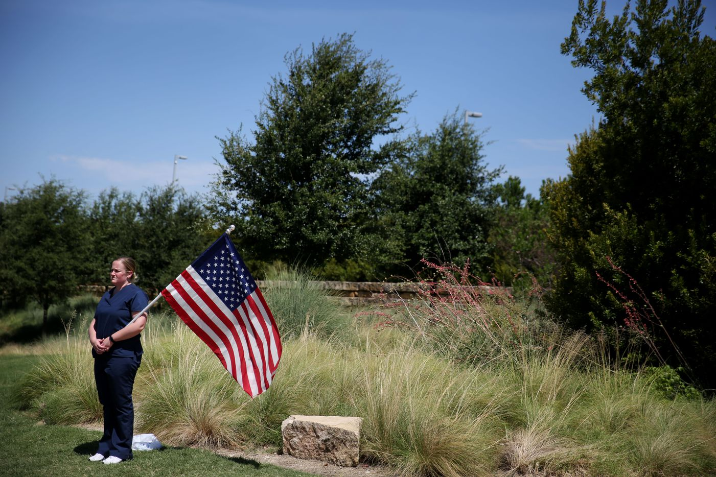 Rebecca Duncan, of Carrollton, Texas, stands outside with the flag of the United States before the funeral for Dallas police sergeant Michael Smith at Watermark Church in Dallas Thursday July 14, 2016. Smith and four other officers were killed during an attack following a peaceful Black Lives Matter protest on July 7. (Andy Jacobsohn/Staff Photographer)