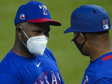 Assistant hitting coach Callix Crabbe (left) wears a face mask as he talks with third base coach Tony Beasley during Texas Rangers Summer Camp at Globe Life Field on Thursday, July 16, 2020.