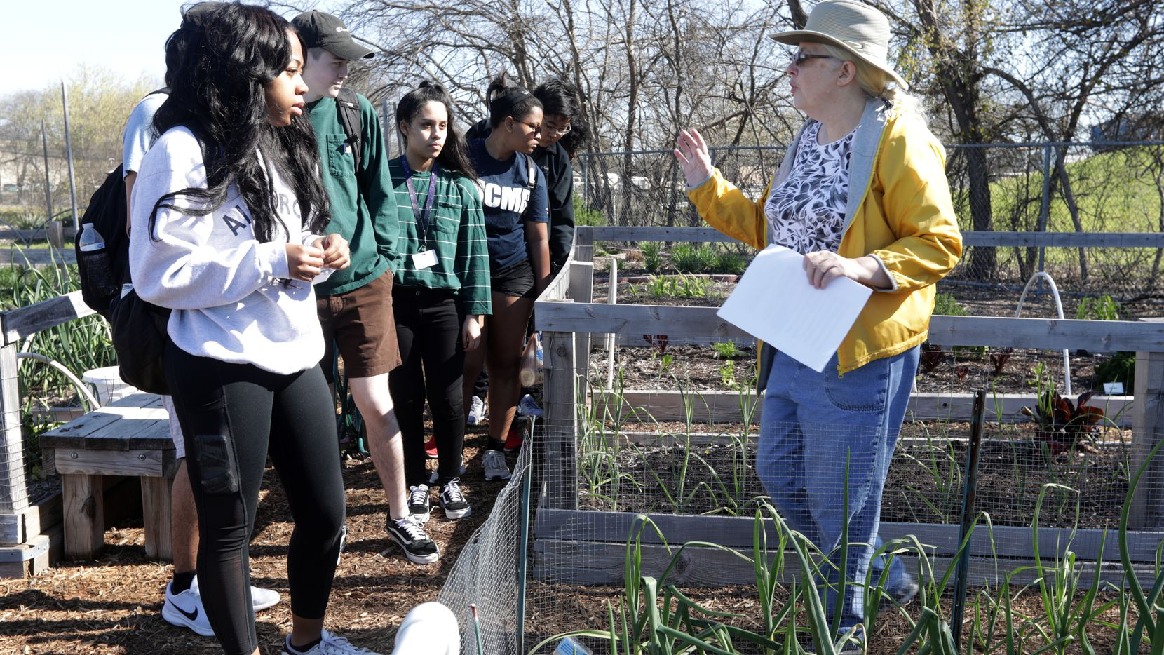 Volunteer Rebecca Brady tours the community gardens with a group of students at the Plano Environmental Education Center in Plano.