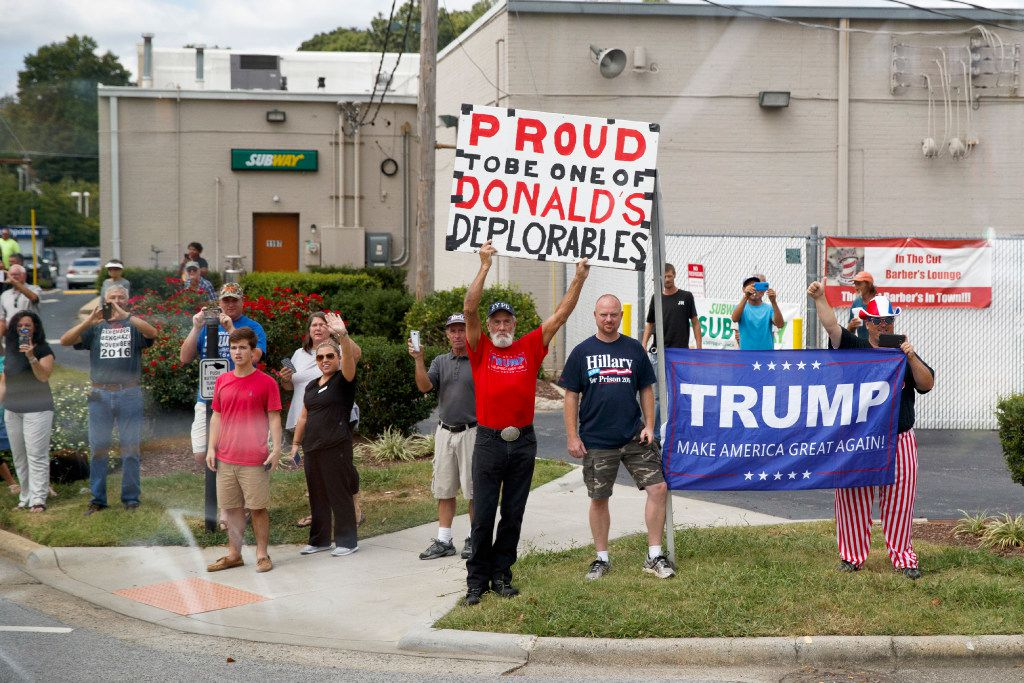 Supporters of Republican presidential candidate Donald Trump holds signs at the motorcade passes to a campaign rally at High Point University, Tuesday, Sept. 20, 2016, in High Point, N.C.