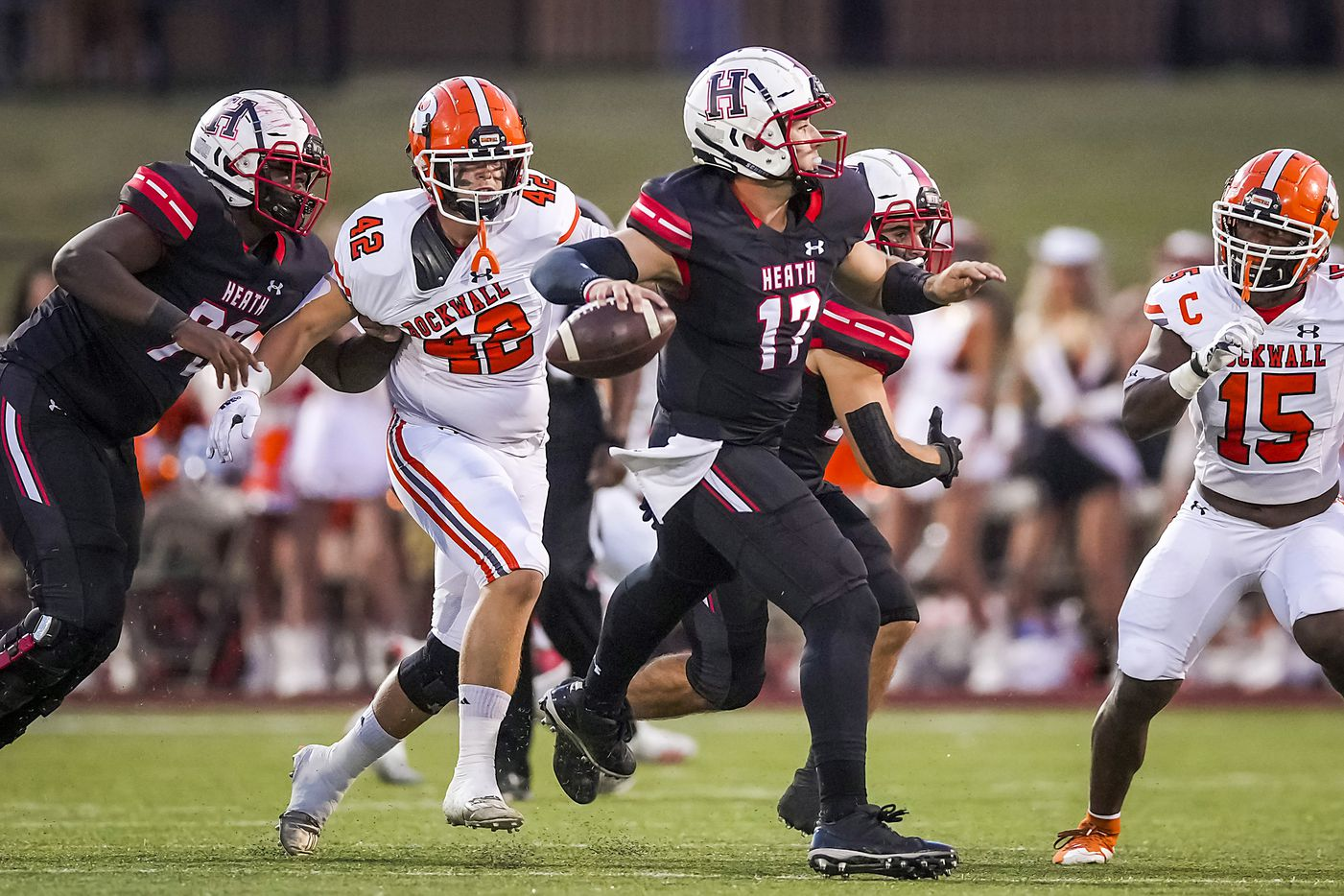 Rockwall-Heath quarterback Josh Hoover (17) scrambles away from Rockwall defensive lineman Robert Buck (42) and linebacker Deyreck Dean (15) during the first half of a District 10-6A high school football game at Wilkerson-Sanders Stadium on Friday, Sept. 24, 2021, in Rockwall.