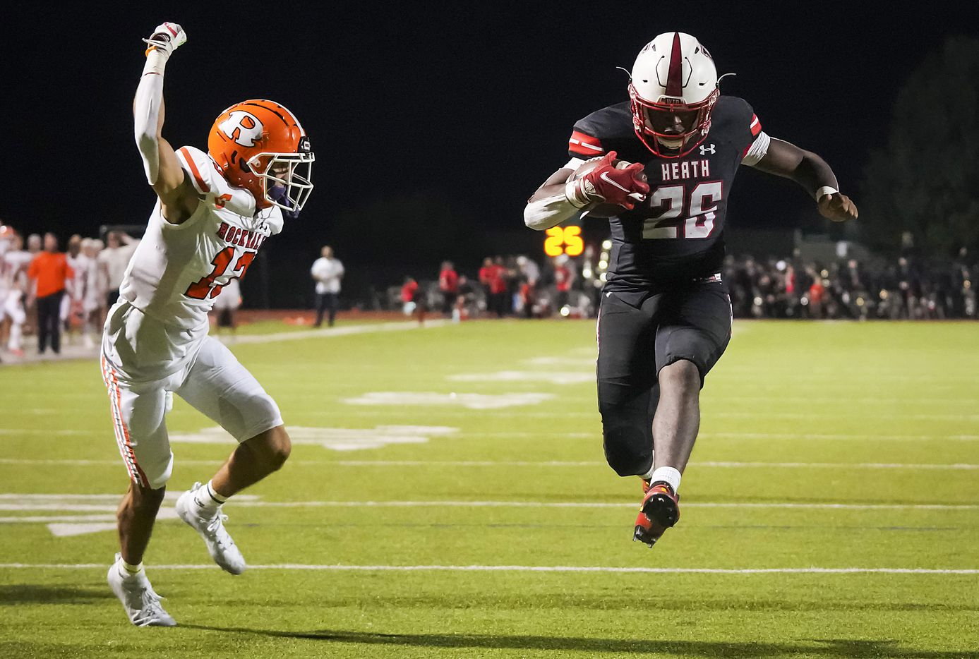 Rockwall-Heath running back  Zach Evans (26) scores on a 3-yard touchdown run past Rockwall defensive back Cadien Robinson (13) during overtime in a District 10-6A high school football game at Wilkerson-Sanders Stadium on Friday, Sept. 24, 2021, in Rockwall.  Rockwall-Heath won the game 79-71 in double overtime.