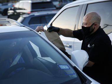 TJ's Seafood Market and Grill manager Scott Gonzalez delivers a curbside order at the Oak Lawn location in Dallas, Friday, November 20, 2020. Conflicting messages on COVID-19 leave Dallas restaurateurs weary and uncertain. Restaurant operators are caught between vocal industry leaders and advice from local officials. (Tom Fox/The Dallas Morning News)