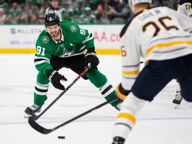 The Dallas Stars' Tyler Seguin (91) looks to get the puck from the Buffalo Sabres' Rasmus Dahlin (26) during the first period on Thursday, Jan. 16, 2020, at the American Airlines Center in Dallas. (Ashley Landis/Dallas Morning News/TNS)