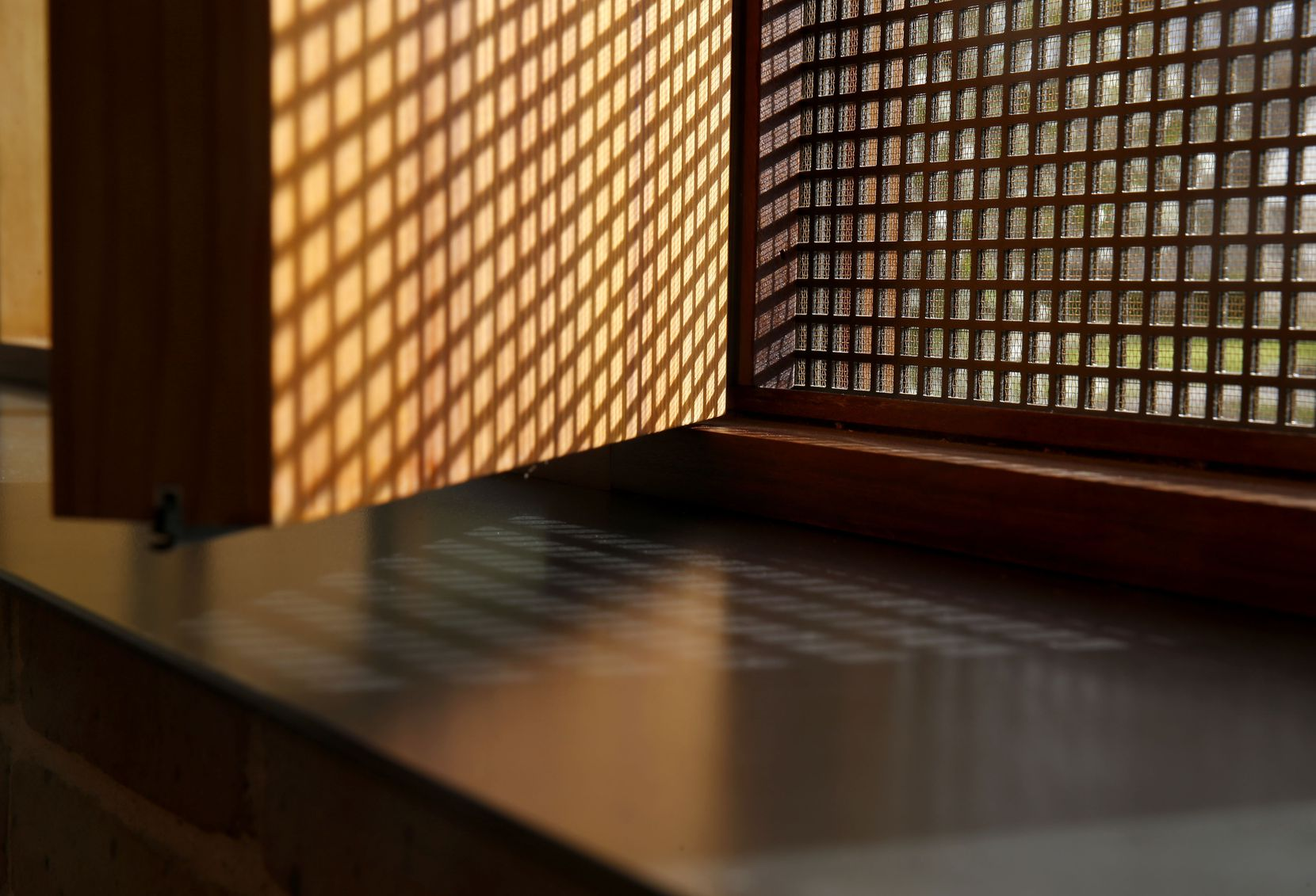 Morning light filters through a perforated steel screen, casting shadows onto a wooden vent door which opens to allow fresh air into the home. The vents also allow in sounds of the neighborhood, while a tight-knit bronze screen prevents insects.