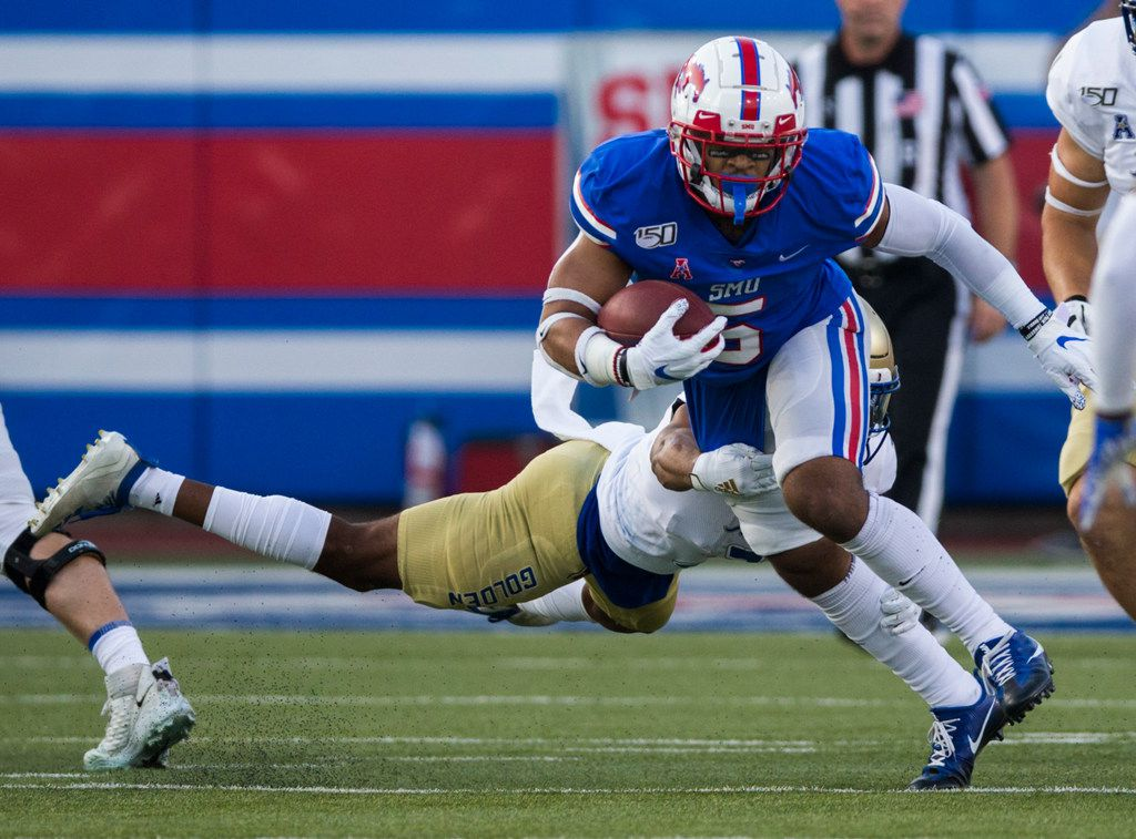 SMU Mustangs running back Xavier Jones (5) is tackled by Tulsa Golden Hurricane safety Cristian Williams (3) during the first quarter of an NCAA football game between Tulsa and SMU on Saturday, October 5, 2019 at Ford Stadium on the SMU campus in Dallas. (Ashley Landis/The Dallas Morning News)