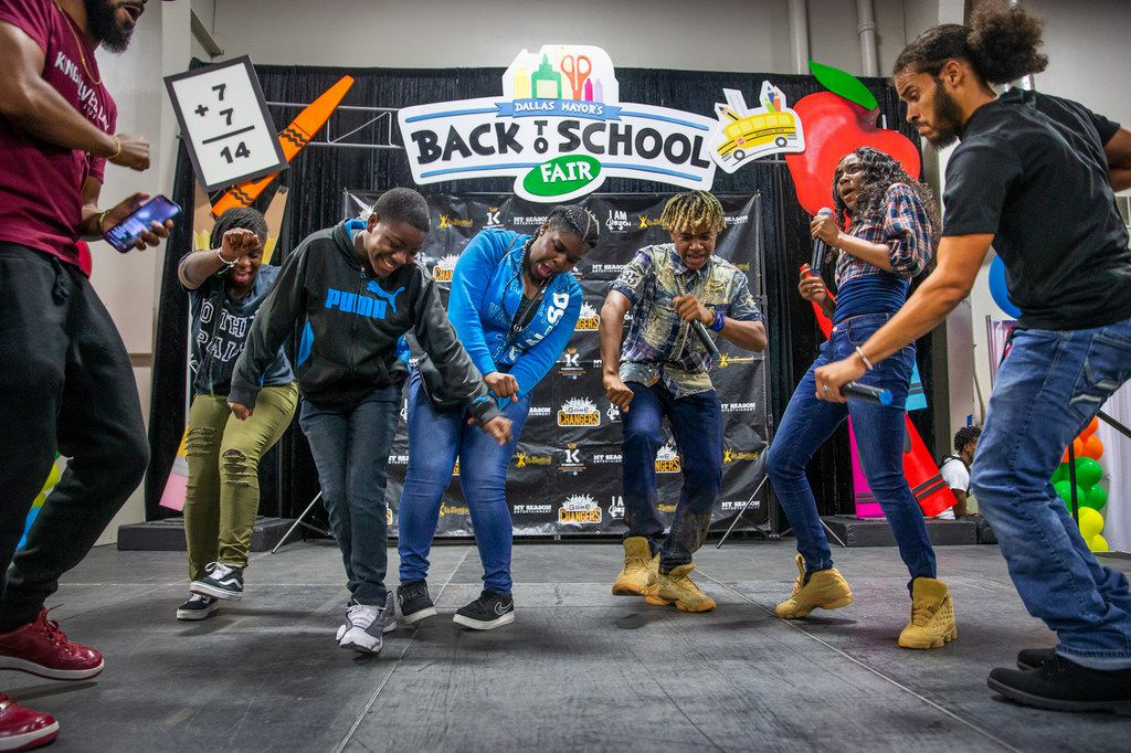 The performers Ax2 and Dejah (third and second from right, respectively) dance with attendees during the 23rd annual Mayor's Back to School Fair at the Fair Park Centennial Hall in Dallas on Friday, Aug. 2, 2019. Thousands of children and their family members were expected to attend, and the event included health and eye screenings, dental screenings, backpack giveaways and more.