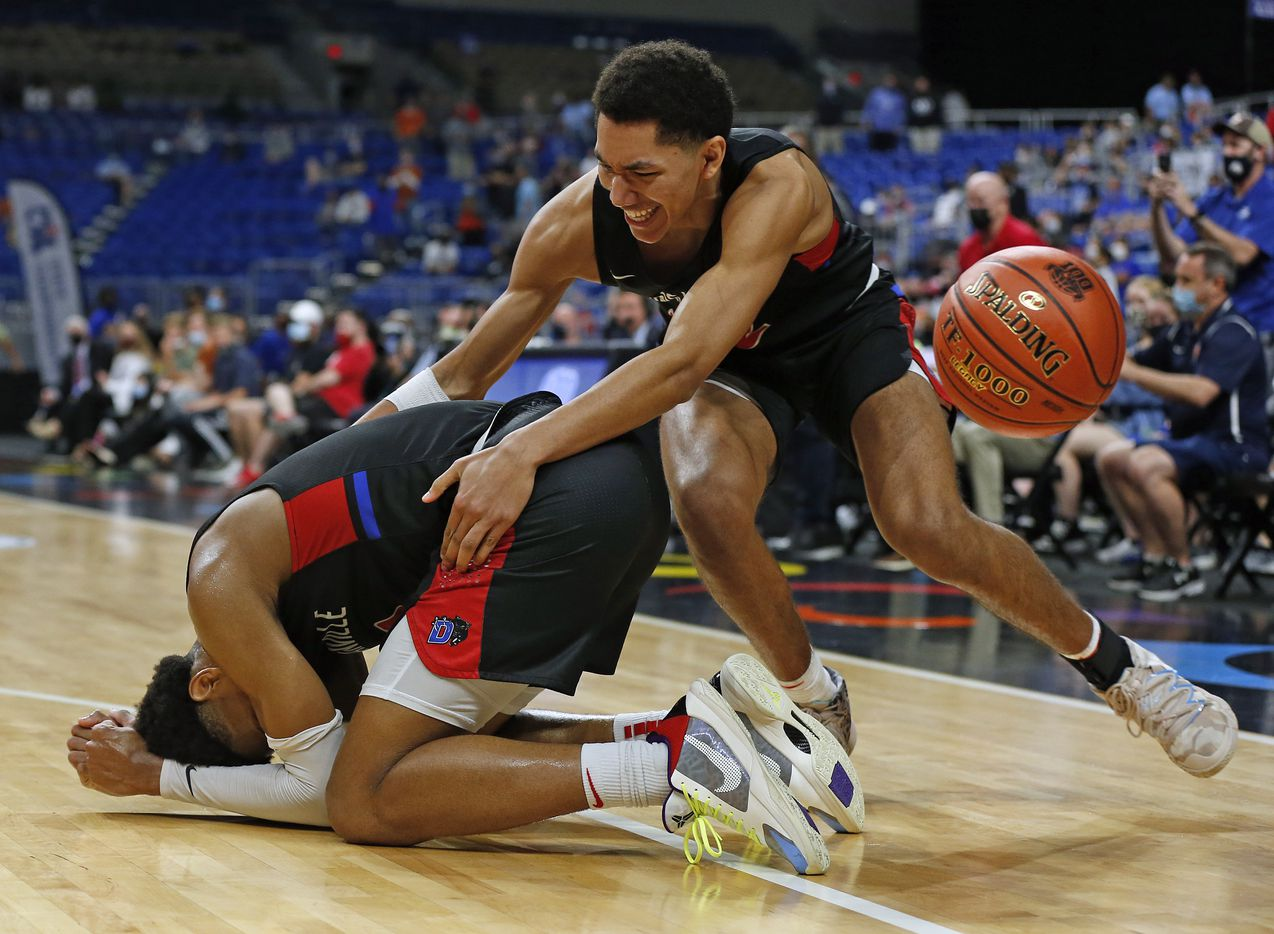 Duncanville Zhuric Phelps #0 fell to the floor as teammate Duncanville Davion Sykes #22 goes to celebrate within as the game ended. UIL boys Class 6A basketball state championship game between Duncanville and Austin Westlake on Saturday, March 13, 2021 at the Alamodome.